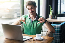 Dislike! Young Dissatisfied Businessman In Green T-shirt Sitting, Working And Looking At Laptop Screen And Showing Thumbs Down. Business And Freelancing Concept. Indoor Shot Near Big Window At Daytime