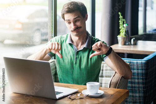 Obraz na plátně Dislike! Young dissatisfied businessman in green t-shirt sitting, working and looking at laptop screen and showing thumbs down