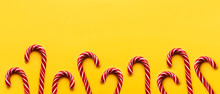Banner With Christmas Candy Cones On Yellow Background. Colorful Holiday Sweets With Bright Copy Space. Traditional Dessert Wtih Red And White Stripes.