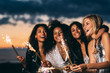 Close up of happy women holding sparklers at sunset