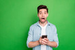 Photo of amazing guy holding telephone read instagram post negative comments not believe eyes open mouth wear denim shirt isolated green color background