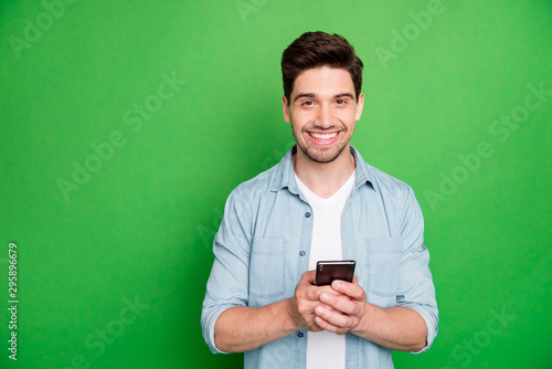 Fotomural  Photo of cheerful brown haired handsome blogger browsing through his telephone l