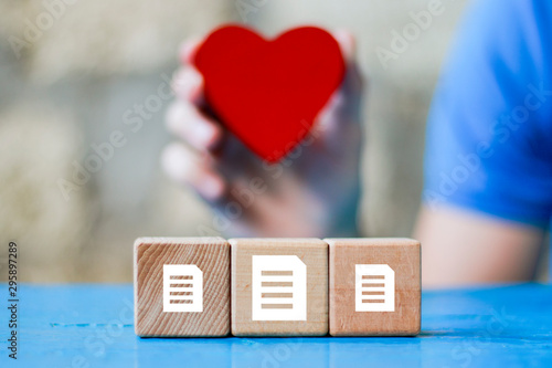 Obraz na plátně  Business file icon on wood block, healthcare service in the background of the heart
