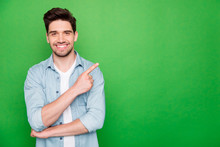 Photo Of Positive Cheerful Attractive Handsome Man Pointing At Empty Space With Forefinger Smiling Toothily With Bristle Isolated Over Green Color Vivid Background