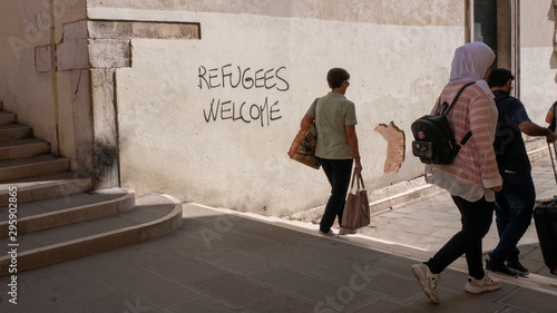 Canvas Print Graffiti with the political slogan Refugees Welcome on a wall in Venice