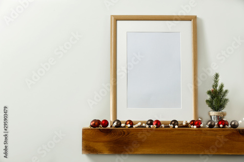 Christmas decorations in bright shiny colors with Christmas lights, picture frames and blurred white wall background Fotobehang