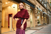 Beautiful Stylish Blond Girl In Knitted Sweater Confidently Looking In Camera On Street