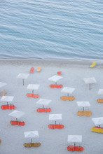 White Parasols With Yellow And Orange Beach Chairs On A Beautiful Sandy Beach, No People