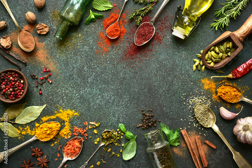 Leinwand Poster Variety of natural organic spices on a spoons on a dark green slate, stone or concrete background