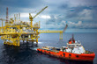 canvas print picture - The shipping box is loaded from an offshore oil rig to the supply vessel at sunset.