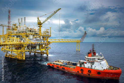 Canvas Print The shipping box is loaded from an offshore oil rig to the supply vessel at sunset