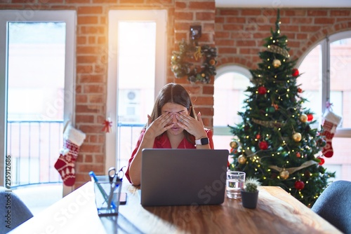 Photo  Beautiful woman sitting at the table working with laptop at home around christmas tree rubbing eyes for fatigue and headache, sleepy and tired expression