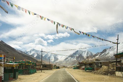 plakat Tibetan and indian people walking beside road of Tsati village on khardung la pass while winter season at Leh Ladakh in Jammu and Kashmir, India