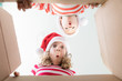Leinwanddruck Bild - Surprised children unpack Christmas gift box
