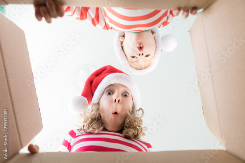 Fotografie, Tablou Surprised children unpack Christmas gift box