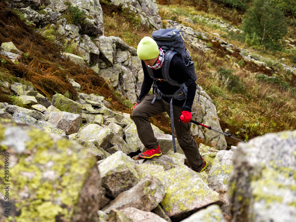 Fototapety, obrazy: Active adult man with backpack and trekking poles walking on rocky stones river
