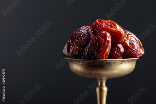 Fotografía  Closeup sweet dried dates in brass dish.