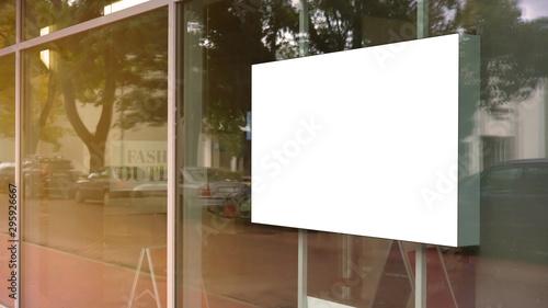 Fotografía  empty white poster frame on glass of showcase window of shopping mall fashion ou