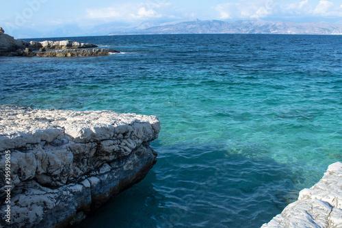 Fototapeta Seascape - a cozy bay in the Ionian Sea, rocks, rocky shore, clear emerald clear water, blue flag, beach, Corfu, Greece obraz