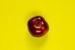 Leinwandbild Motiv one red apple on an isolated yellow background