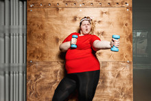 Funny Fat Girl Dressed In The Sportswear And With A Bandage On Her Head Stands With Dumbbells On The Background Of A Wooden Wall In The Gym