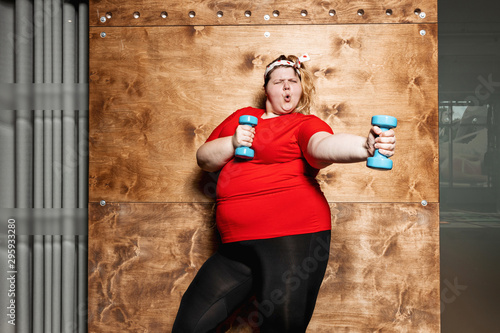 Fotografija Funny fat girl dressed in the sportswear and with a bandage on her head stands w