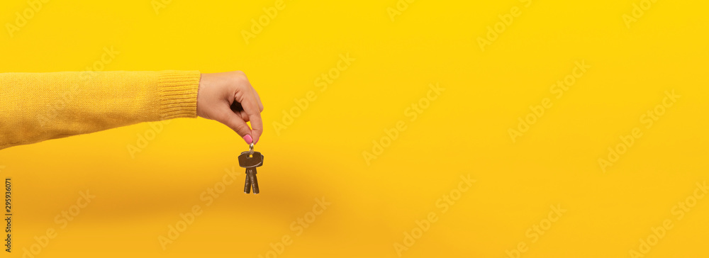 Fototapety, obrazy: female hand holding house keys, suggesting, over yellow background, panoramic image.
