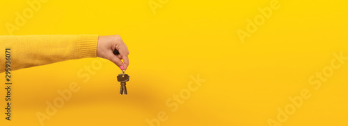 female hand holding house keys, suggesting, over yellow background, panoramic image.