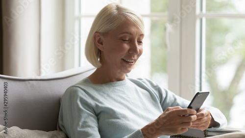 Photographie  Happy mature woman sitting on cozy couch, using smartphone.