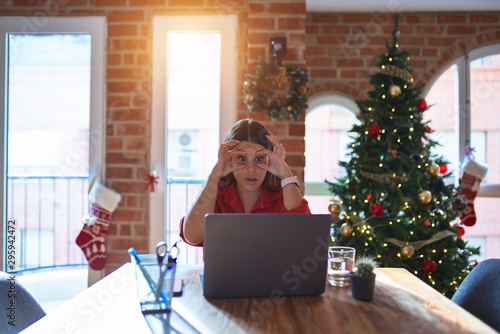 Fotografie, Obraz  Beautiful woman sitting at the table working with laptop at home around christma