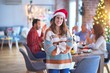 Young beautiful woman smiling happy and confident. Standing wearing santa hat celebrating Christmas with family at home