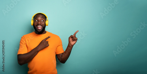 Leinwand Poster Boy with yellow headset listens to music and indicates something