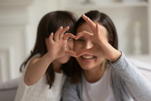 Happy Young Mother With Little Daughter Making Focused Heart Sign.