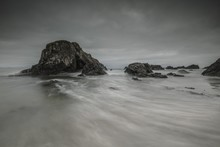 Beautiful Shot Of Rock Formations On The Body Of Water With Flowing Movement Under A Gray Cloudy Sky