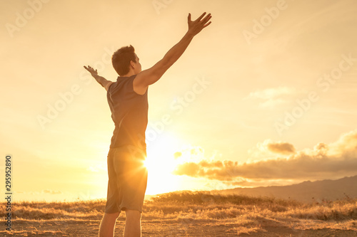 Cuadros en Lienzo Happy man looking up to the sky with arms raised up to the sunset
