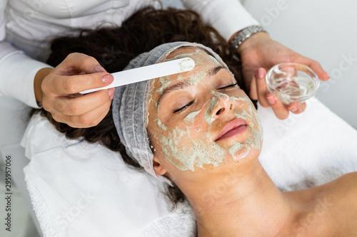 Cuadros en Lienzo Beautiful woman receiving natural green peel facial mask with rejuvenating effects in spa beauty salon