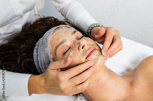 Beautiful woman receiving natural green peel facial mask with rejuvenating effects in spa beauty salon Canvas Print