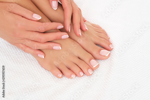 Foto op Canvas Pedicure Perfectly done manicure and pedicure on female feet isolated on white background.