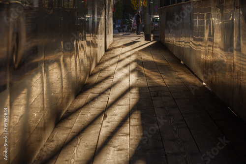 Golden sunlight with strong shadow and silhouette view of narrow sidewalk between temporary wall of construction site beside the street in city.
