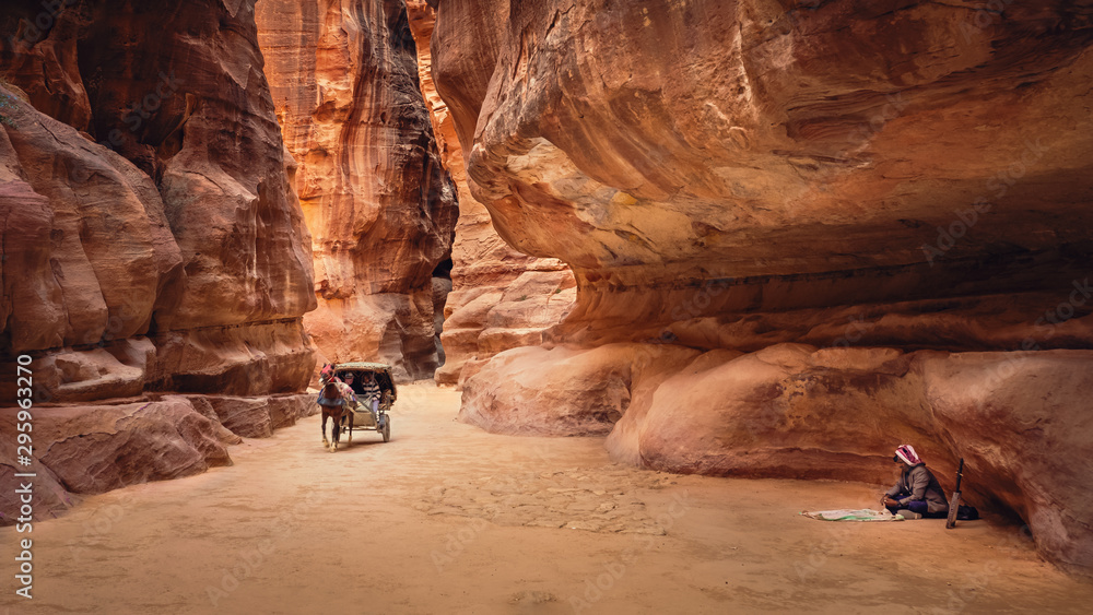 Fototapety, obrazy: The Siq with a horse-drawn cart for transporting tourists and a rababa player, Petra, Jordan