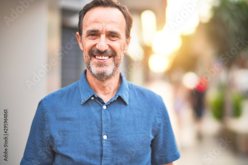 Fotomural  Middle age handsome man standing on the street smiling