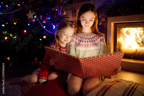 Cuadros en Lienzo Happy young sisters reading a story book together by a fireplace in a cozy dark living room on Christmas eve