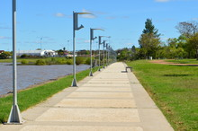 Sidewalk With Lampposts On The Shore Of The Lake.