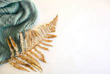 Leaf Of Golden Trendy Fern And Blue Knitted Scarf Against White Background. Minimal Flat Lay, Top View.