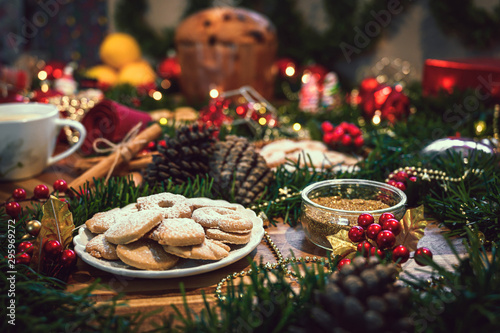 Christmas ingredients table with a cookies in the center on a wooden board, accompanied by orange, panettone, cinnamon, pine. Festive pine decoration on red rustic background