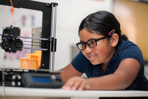 Fototapeta A happy young girl wearing glasses and watching a 3d printer finish the 3d model she created. obraz
