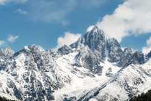 Panoramic Snow Mountain With White Clouds And Blue Sky