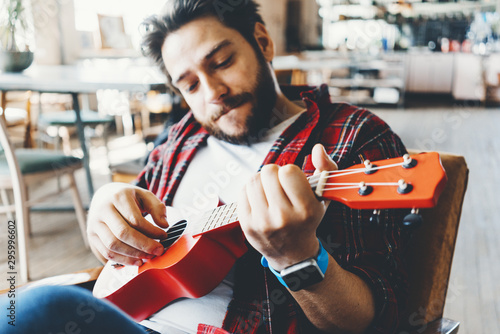 Portrait of happy man with flannel shirt playing ukulele in big room - 295996602