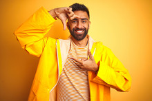 Young Indian Man Wearing Raincoat Standing Over Isolated Yellow Background Smiling Making Frame With Hands And Fingers With Happy Face. Creativity And Photography Concept.