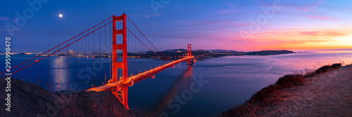 Golden Gate Bridge in San Francisco under full moon in sunset sky panorama